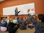 Student raises hand to answer question during an interactive writing session at 2015 YWAC.