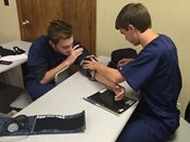 Two male students practicing taking blood pressure.