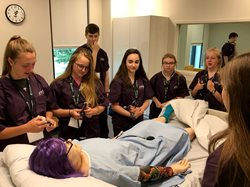 Students holding stethoscopes looking over a practice dummy on a gurney.