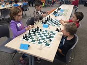 Chess Tournament: Students playing chess at tables