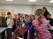 Students gather around 2015 YWAC presenter as she demonstrates how to create a dream catcher.