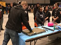 Students gather around a table to work with concrete.