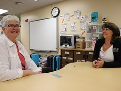 Dremel 3D printer winner Beth Sletta sits at desk in her classroom with Cindy Ehlers