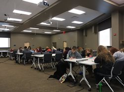 Students writing at desks in the conference center.