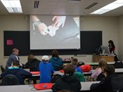 Students learn origami watching presenter's hands on projected screen.